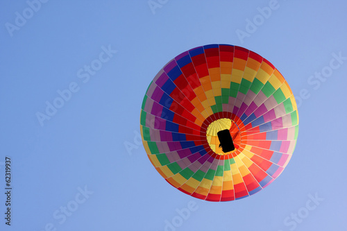 Poster Ballon rainbow hot air balloon in a blue sky seen from below.