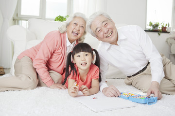 .Senior couple with granddaughter drawing.