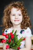 Smiling girl with red tulips in blackboard background.