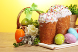 Beautiful Easter cakes, colorful eggs in basket and candles
