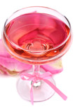Composition with pink sparkle wine in glass and  rose petals