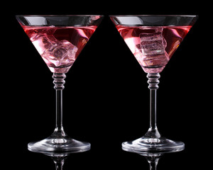 Red cocktail in martini glasses isolated on black
