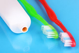 Toothbrushes and paste on blue background