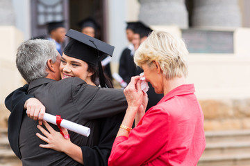 young female graduate hugging her father