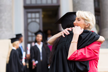 young female graduate hugging mother
