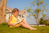 little girl sitting and reading a book on nature