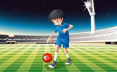 A boy kicking the ball with the flag of Turkey