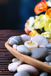 Composition with  spa stones and candles in wooden bowl, near