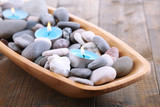 Wooden bowl with Spa stones, sea shells and candles