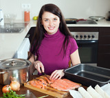 Woman cutting salmon for fish pie