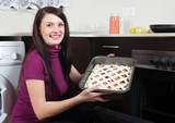 Smiling woman putting fish pie on roasting pan into oven