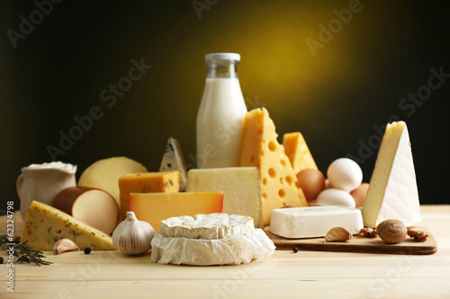 Deurstickers Egg Tasty dairy products on wooden table, on dark background