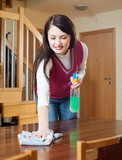 brunette girl cleaning table with cleanser