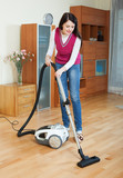 full length shot of woman cleaning with vacuum cleaner