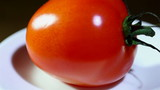Tomato turns on a white plate close up