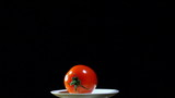 Red Tomato turns on  white plate, black background ,close up