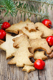 Christmas cookies on wooden table under fir branch.