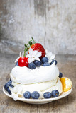 Meringue decorated with blueberries, strawberries and orange