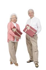 .Senior couple holding gift box.