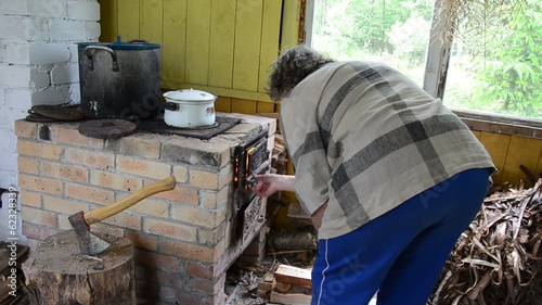 senior woman prepare food put firewood in rural kitchen stove