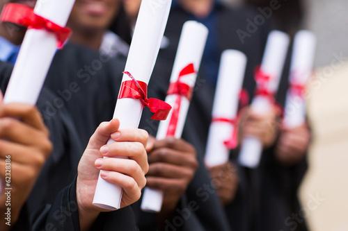 Leinwanddruck Bild group of graduates holding diploma