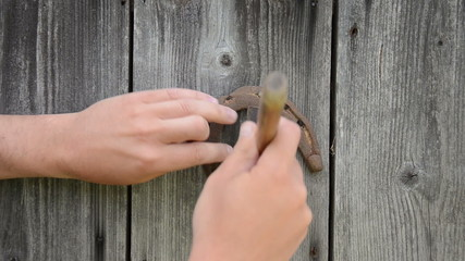 man hand with hammer take horse shoe symbol of luck wood wall