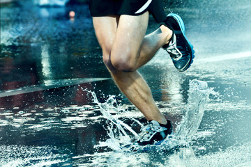 Runner running through puddle