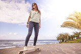 beautiful young skater woman with a longboard near the sea
