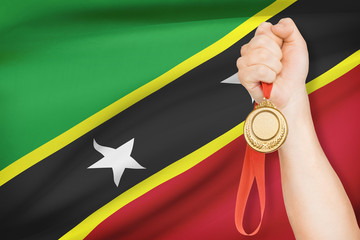 Medal in hand with flag - Saint Christopher and Nevis