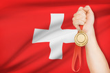 Medal in hand with flag on background - Swiss Confederation