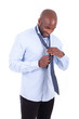 Portrait of a young African American business man knotting a tie