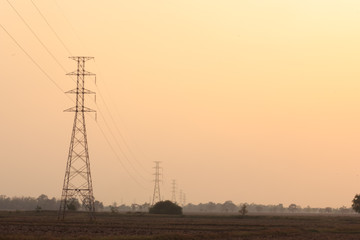 High voltage power pole middle of a cornfield at sunset.