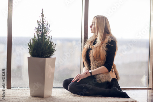 Beautiful blond woman with a cap of tea near the window
