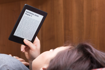 Girl is reading with an Ebook Reader on the bed