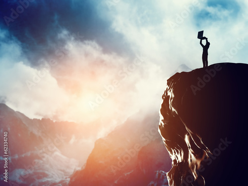A man standing with laptop on the peak of a mountain at sunset