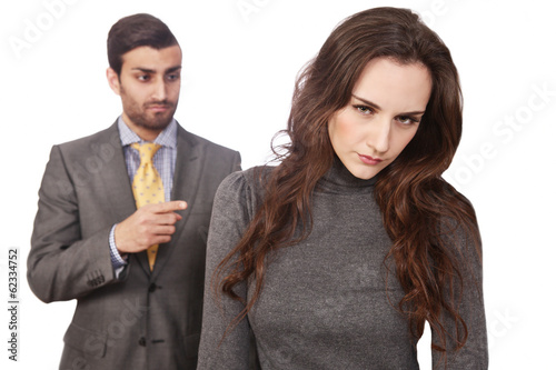 Young woman fired, with angry boss in background