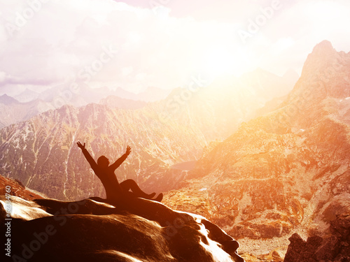 A happy man sitting on the peak of a mountain with hands raised
