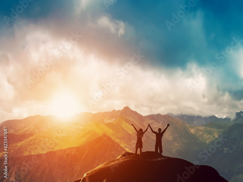 Leinwandbild Motiv Happy couple together on the peak of a mountain at sunset