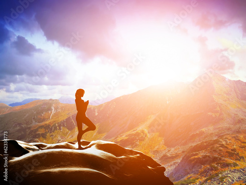 Woman standing in tree yoga position, meditating in mountains