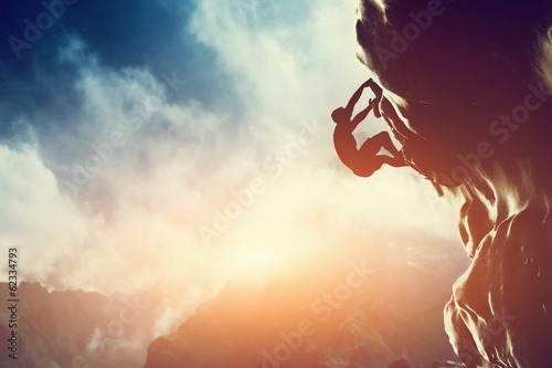 A silhouette of man climbing on rock, mountain at sunset. - 62334793