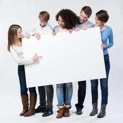 junge frau zeigt freunden etwas auf einem schild