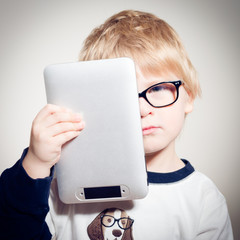 Child boy in glasses holding tablet pc