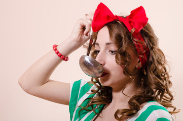 Happy beautiful young pinup woman with ladle