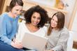 drei freundinnen schauen zusammen auf laptop