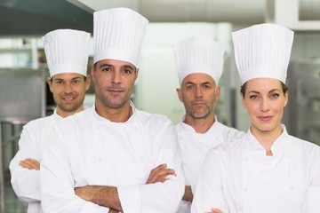 Happy team of chefs looking at the camera