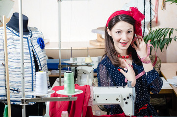Funny young pinup woman with sewing machine and measuring tape