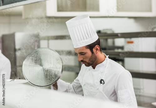 Handsome chef lifting a lid off a pot
