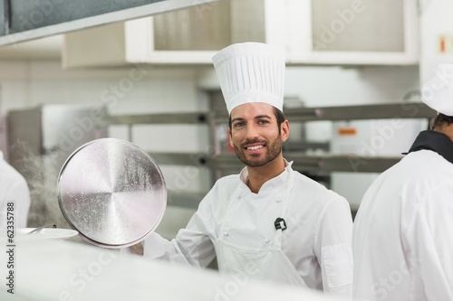 Happy chef lifting a lid off a pot