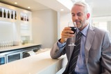 Mature businessman smelling wine at bar counter