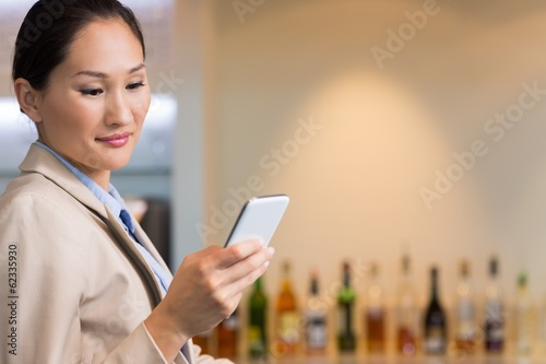 Closeup of a young businesswoman text messaging